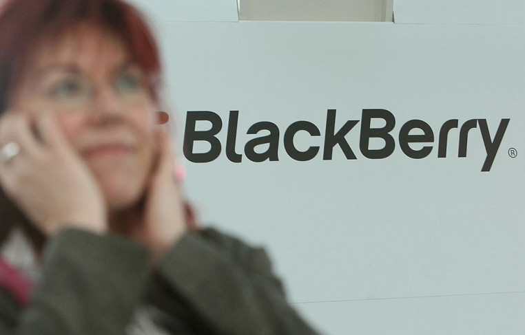 A visitor talks into a mobile phone next to the BlackBerry stand.