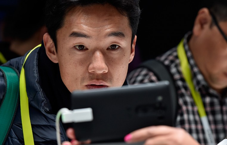 An attendee looks at the LG V10 smartphone at the LG booth at CES 2016.